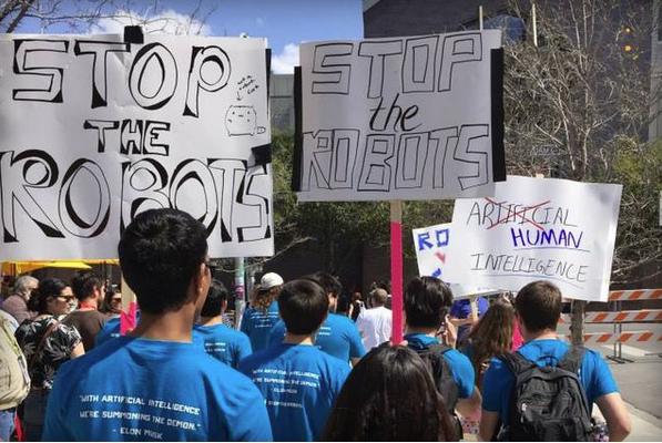 「ロボットをくい止めろ」と書かれたプラカードを掲げて行進する人々(http://www.theverge.com/)