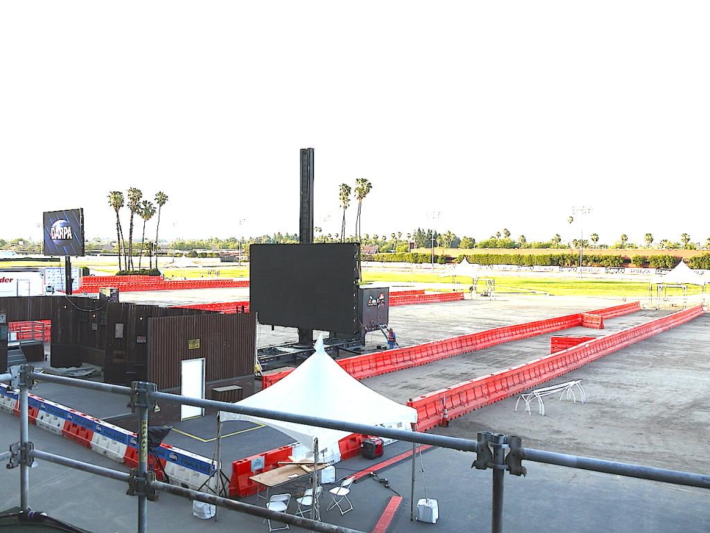 右側の長い長いトラックの先からロボットが車を走行。手前で降りて、左側ののドアを開けて一連のタスクを遂行する。