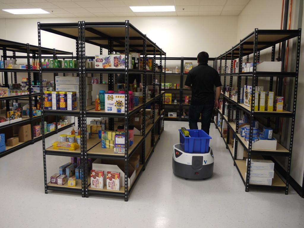 作業テスト中のフライト。作業員の後をついていって、ピッキングされた商品を容器で受ける。
