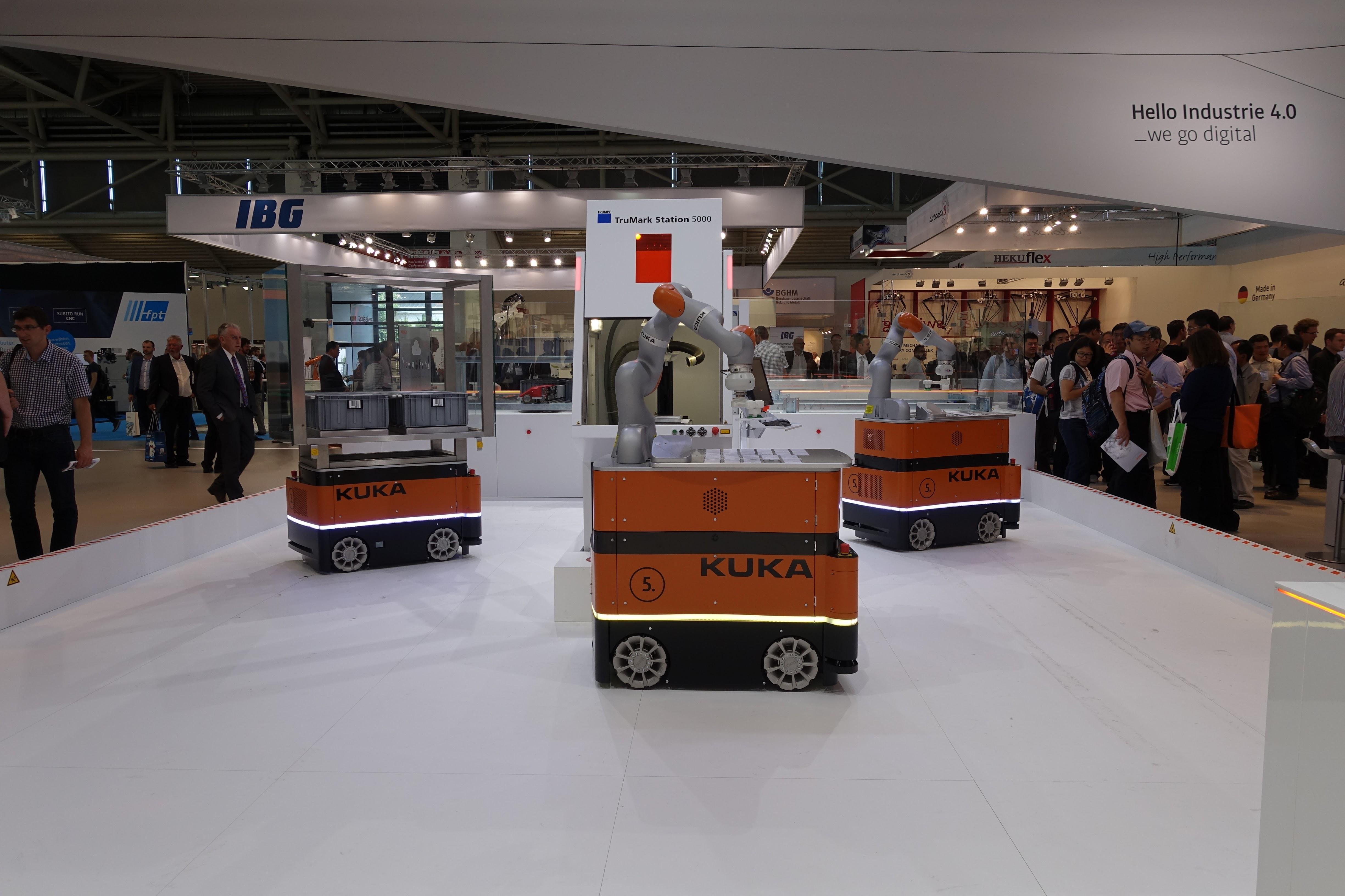アーム付きの自律走行型ロボットが、連携して作業中。