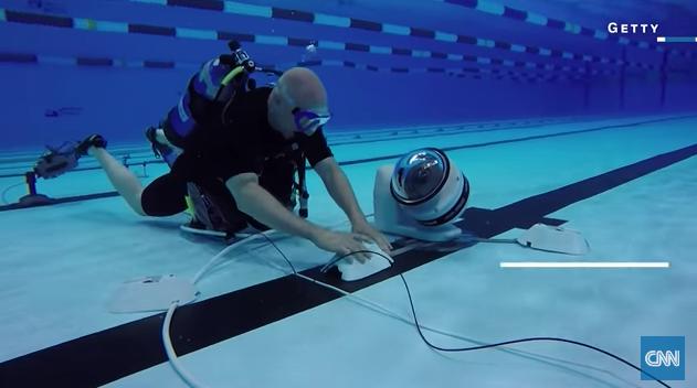 プールでロボット・カメラをセット中。(http://money.cnn.com/より)